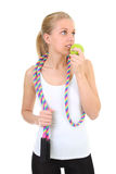 Girl with skipping rope biting apple Royalty Free Stock Image
