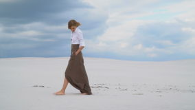 A girl in a skirt and blouse walks barefoot slowly across the desert stock footage