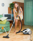 Girl  in skirt cleaning with vacuum cleaner Royalty Free Stock Image