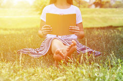 Girl in skirt sitting on the grass in the Park and reading a book. Concept of learning and leisure Royalty Free Stock Images