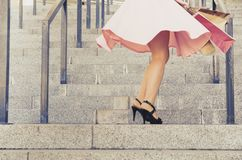 A girl in a skirt spins on stairs with paper packages Stock Images