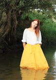 Girl in skirt in water. Young woman - dreaming girl in skirt standing in water of stream stock photo