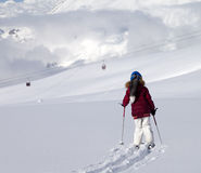 Girl on skis in off-piste slope with new fallen snow at sun day Stock Image