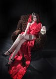 Girl with skull. Girl in red gown with skull Stock Image