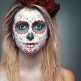 Girl with a skull face makeup. Beautiful girl with a skull face makeup Stock Image