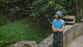 The girl in a skullcap, a blue jacket and a cape on a waist travels around the island of Bali. She costs on a terrace at stock video footage