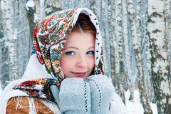 Girl - Slavic appearance smiles. wrapped in a scarf in winter royalty free stock photography