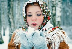 Girl in Slavic style in a scarf blows snow from mittens. stock photos