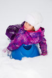 Girl on a Sled. Cute little girl on a sled royalty free stock image