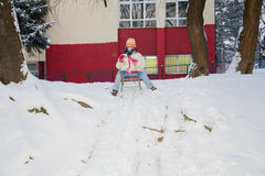 Girl On A Sled Playing In The Snow Royalty Free Stock Image