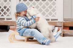 Girl on a sled with a small dog Stock Photography