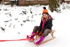 Girl on sled in the snow Stock Photography