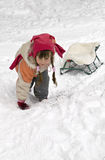 Girl with a sled up the hill. Little girl with a sled climbs a snow-covered hill Stock Photography