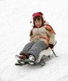 Girl sledding. The little girl sledding down a hill Stock Photos