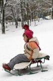 Girl sledding. The little girl sledding down a hill Stock Photo