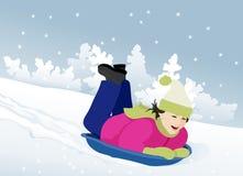 Girl sledding. Little girl sledding in the snow slope Stock Image