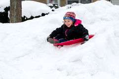 Girl sledding down a hill Royalty Free Stock Photo