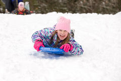 Girl Sledding Head First and Looking at Camera Royalty Free Stock Photography