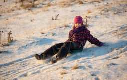 Girl sledding in the light of sunset Royalty Free Stock Photos