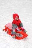 Girl sledding for a sledge Stock Photography
