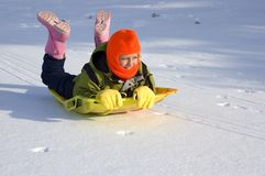 Girl Sledding on Snow Covered Lake. Cute young girl dressed in colorful winter clothes sledding on snow covered lake Royalty Free Stock Photo