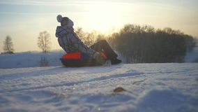 Girl sledding in winter park, young happy woman tobogganing on the mountain through the sun in slow motion during stock video