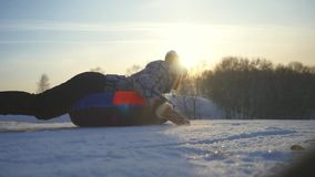 Girl sledding in winter park, young pretty woman tobogganing on the mountain through the sun in slow motion during stock video