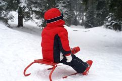 Girl with sledge. Two and a half year old girl playing with a red sledge Stock Image