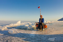 Girl with a sledge and trekking pole is on the ice of Lake Baika Stock Images