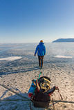 Girl with a sledge and trekking pole is on the ice of Lake Baika Royalty Free Stock Image