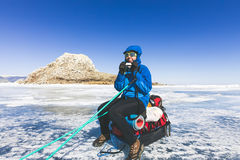 Girl with a sledge and trekking pole is on the ice of Lake Baika Royalty Free Stock Photo