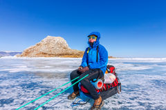 Girl with a sledge and trekking pole is on the ice of Lake Baika Stock Photo