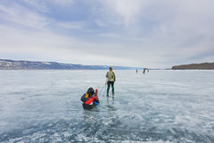 Girl with a sledge and trekking pole is on the ice of Lake Baika Royalty Free Stock Photography