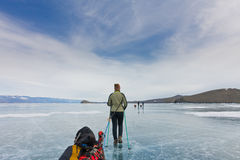 Girl with a sledge and trekking pole is on the ice of Lake Baika Stock Photos