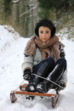 Girl on sledge. Young girl sledging in the snow Royalty Free Stock Photo