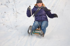 Girl sledging down hill Stock Photos