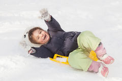 Girl sledging down hills winter. Cute little girl with saucer sleds outdoors on winter day, ride down the hills, overturn on sleds, winter games and fun Stock Images