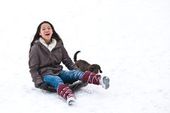 Girl sledging with her dog Royalty Free Stock Photos