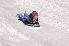 Girl sleds down hill. Royalty Free Stock Photo