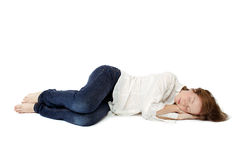 The girl sleep in her clothes on the floor. The girl calmly asleep in your clothes on the floor white background Royalty Free Stock Image