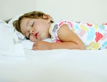 Girl sleeping. In colourful clothes on white bed Stock Photo