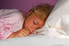Girl sleeping. Indoor portrait of a cute little caucasian girl child sleeping in her bed Stock Photo