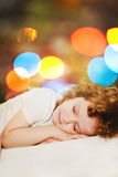 Girl is sleeping. Against the background of the rainbow bokeh. Royalty Free Stock Photo