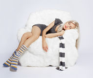 Girl sleeping in arm-chair. Portrait of beautiful blonde sleeping on big white furry arm-chair Royalty Free Stock Photos