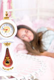 Girl sleeping in bed. Clock on the table and a girl sleeping in bed Stock Photography
