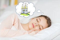 Girl sleeping in bed and dreaming of castle. People, children, rest and comfort concept - girl sleeping in bed at home and dreaming about fairy castle Royalty Free Stock Photos