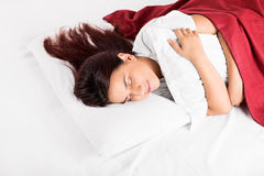 A girl sleeping on a bed hugging a pillow Stock Photo
