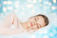 Girl sleeping in bed over blue lights background Royalty Free Stock Image