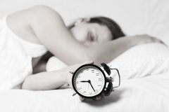 Girl is sleeping in bed and is switching alarm clock. sleepy woman holds alarm clock in her hand and sleeps Royalty Free Stock Images