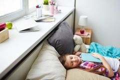 Girl sleeping with book. Beautiful teen girl sleeping in her cozy bedroom with book on her chest Royalty Free Stock Photos
